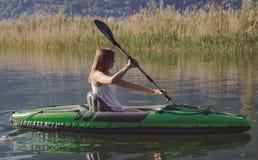 Kayak della giovane donna sul lago fotografie stock libere da diritti