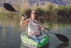 Kayak della giovane donna sul lago fotografia stock