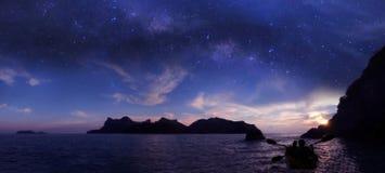 Kayak della madre e della figlia della siluetta nell'oceano con milione galassia delle stelle e cieli di alba immagine stock libera da diritti