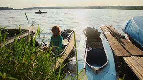 Kayak dock at sunset. Girl waiting in boat, beautiful nature. Stock footage stock video
