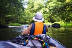 Kayak e canoa Giovane donna in barca con le nuotate dei remi sul fiume selvaggio in giungla Ragazza turistica in canoa con il rem fotografie stock libere da diritti