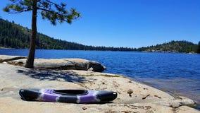 Kayak en rocas con el lago en el fondo fotos de archivo