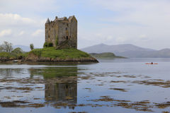 Kayak explores castle stalker loch scotland Stock Photo