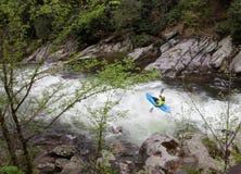 Kayak fahren hinunter die Stromschnellen auf einem Gebirgsfluss lizenzfreie stockfotografie