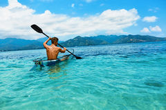 Kayak fahrende Sommer-Reise Mann-Canoeing transparenter Kajak im Ozean lizenzfreie stockbilder