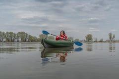 Kayak fishing at lake. Fisherwoman on inflatable boat with fishing tackle.  stock photo
