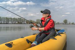 Kayak fishing at lake. Fisherwoman on inflatable boat with fishing tackle.  royalty free stock photos
