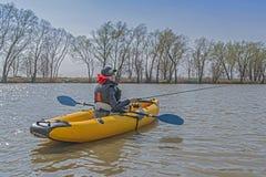 Kayak fishing at lake. Fisherwoman on inflateble boat with fishi. Ng tackle royalty free stock photos
