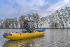 Kayak fishing at lake. Fisherwoman on inflateble boat with fishi. Ng tackle stock photos