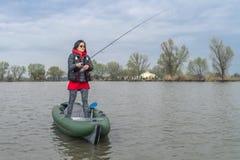 Kayak fishing at lake. Fisherwoman on inflateble boat with fishi. Ng tackle royalty free stock image