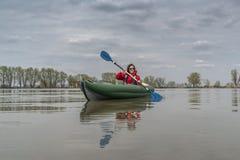 Kayak fishing at lake. Fisherwoman on inflateble boat with fishi. Ng tackle stock photo