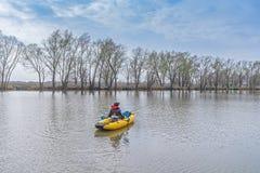 Kayak fishing at lake. Fisherwoman on inflateble boat with fishi. Ng tackle royalty free stock images