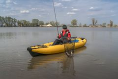 Kayak fishing at lake. Fisherwoman with pike fish on inflatable boat with fishing tackle.  stock images