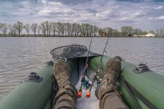 Kayak fishing at lake. Legs of fisherman on inflatable boat with fishing tackle royalty free stock photography