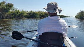 Man in inflatable Kayak fishing. A spinning trip with an inflatable kayak on a delta canal Stock Photography