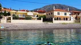 Kayak floating in calm gulf of Corinth Bay, Greece. A kayak floating gently in the calm gently rippled waters of a Corinthian Gulf bay, Ormos Lemonias, Panormos stock footage