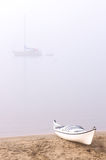 Kayak on foggy beach. Kayak on the beach during a foogy morning with sail boat in background Stock Photo