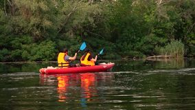 Kayak with a guy and a girl swims on the river. Slow motion stock video footage