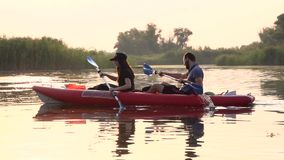 Kayak with a guy and a girl swims on the river . Slow motion stock footage