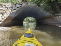 Kayak jaune allant à l'intérieur d'un tunnel Photographie stock libre de droits
