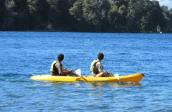 Kayak in a lake. People, family, men women and children kayaking in the lake deep blue water. Enjoing vacaciones, weekend, active sports. Sunny day, clear sky royalty free stock image