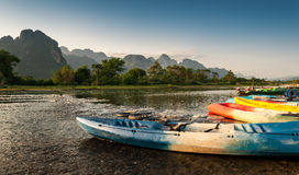 Kayak and longtail boats in Nam Song river. At Vang Vieng, Laos royalty free stock images