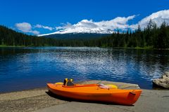 Kayak lying on the ground at Trillium Lake with the Mt. Hood in the background on a sunny day of early summer. Recreation and fish. Ing concept advertisment stock image