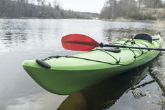 Kayak moored on the shore of the lake, against the backdrop of t. Green kayak is moored on the shore of the lake, against the background of the forest and the Royalty Free Stock Photography