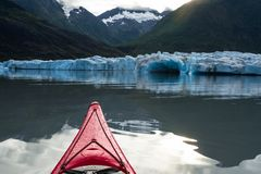 Kayak moving toward the calving face of the Spencer Glacier in A. A red kayak floating in the terminal lake of the Spencer Glacier points toward the calving Royalty Free Stock Image