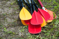 Kayak oars and paddles on the river bank. Colored kayak oars and paddles on the river bank Stock Photo