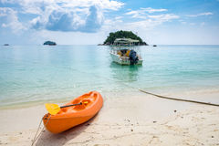 Kayak orange boat with speed boat anchor on white sand Stock Images