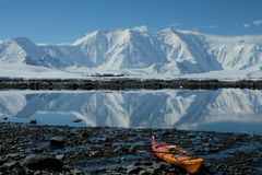 Kayak orange de l'Antarctique dans une baie bleue de miroir photos stock