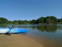 Kayak and paddle on beach with green trees and lake Stock Images