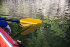 Kayak paddle reflection on lake. Yellow kayak paddle and its reflection in the water royalty free stock images