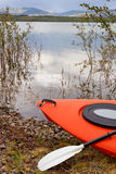 Kayak and paddle in willow bushes alongside a lake Royalty Free Stock Image