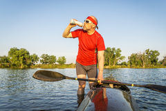 Kayak paddler drinking water. Senior kayak paddler drinking water or sport drink after paddling workout on a lake in summer Stock Photography