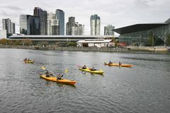 Kayak Paddlers On Yarra River, South Wharf, Melbourne, Victoria, Australia. Coastal Cityscape Of Skyscrapers In South Bank Royalty Free Stock Photography