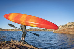 Kayak portaging on lake shore Stock Images
