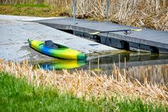Kayak Ready to be Launched in Lake. A blue, green and yellow Kayak getting ready to be launched into a lake.  The paddle is sitting on the pier next to the Kayak royalty free stock photography