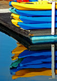 Kayak Reflections. A Stack of Kayaks creating a Mirror Reflection in Calm Water stock image