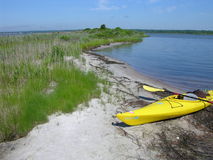 Kayak resting on the shore of Ninigret Pond. Taking a break on a hot summer day, the yellow kayak complements the vibrant blue water and turquoise summer sky Royalty Free Stock Photography