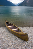 Kayak rests on a shore of mountain lake Royalty Free Stock Photos