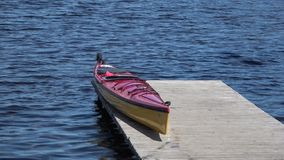 Kayak rests on a wooden pier on the lake stock footage