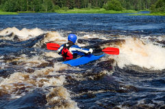 Kayak on river. Kayaker sporting a kayak cuts through water Stock Photos