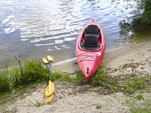 Kayak on the river bank. Red kayak on the river bank Royalty Free Stock Images