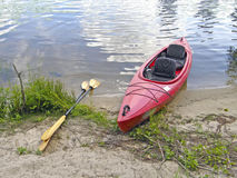 Kayak on the river bank. Red kayak on the river bank Stock Photos
