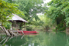 Kayak in river. Kayak in green river near raft and house Royalty Free Stock Images