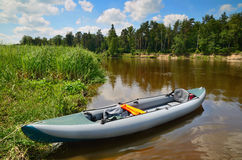 Kayak on the river's shore. An inflatable kayak on the shore of the Neman river in Belarus with wood landscape on background Royalty Free Stock Images