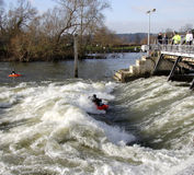 Kayak on River Weir. Man Paddling a kayak on Whitewater on a River Weir in England with spectators looking on Stock Photo