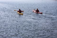Kayak rowers on a kayak paddling by the sea, active water sport and leisure, kayaking Royalty Free Stock Photography